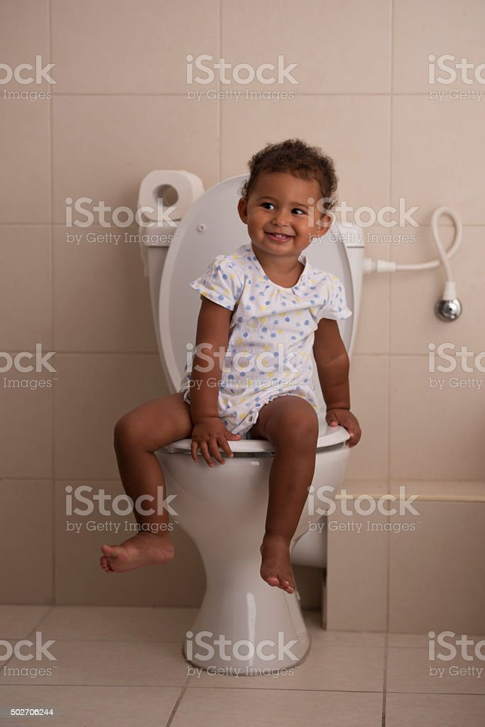Steps of baby development. Little baby girl on the toilet. stock photo