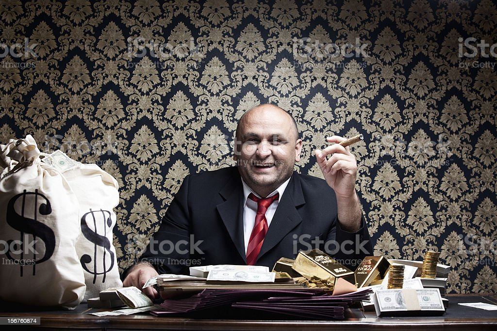 Stereotype Rich Man Posing With Money Bags And Dollar Bills royalty-free stock photo