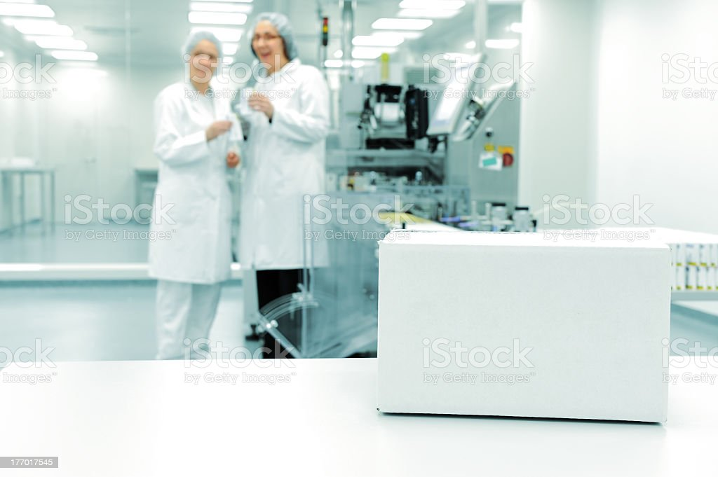Sterile factory with white box in foreground and two workers stock photo
