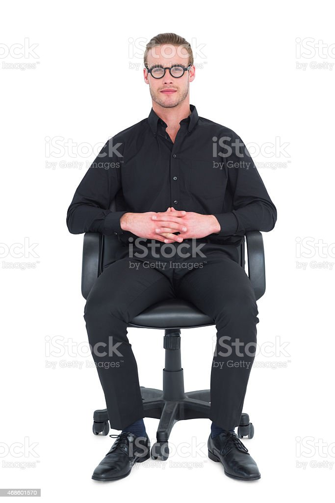 Stern businessman sitting on an office chair stock photo