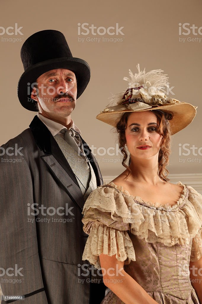 Stern Victorian man and demure wife pose in formal dress stock photo