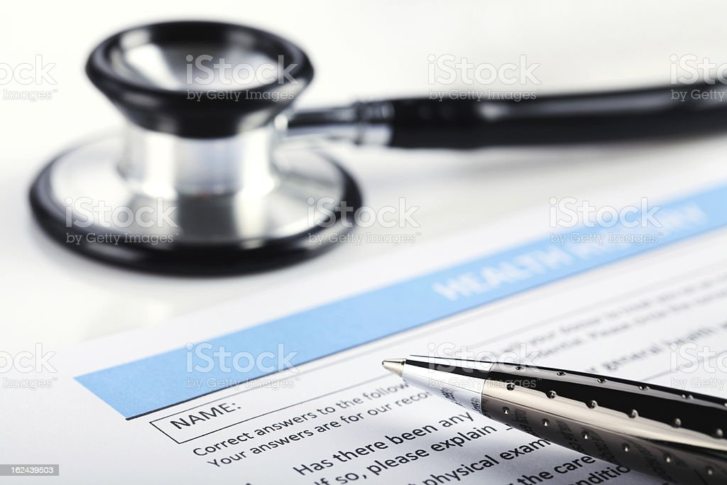A stethoscope and a pen on top of a medical form royalty-free stock photo