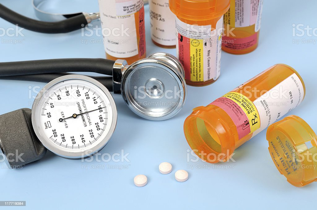 A stethoscope and blood pressure meter next to medication stock photo