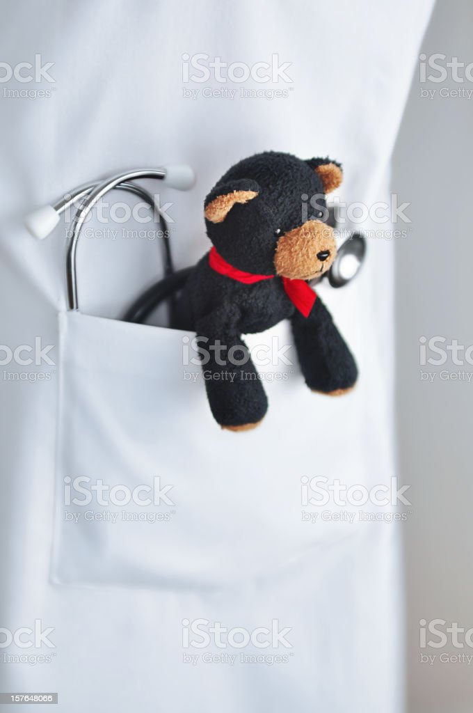 Stethoscope and child's teddy bear in doctor's lab coat pocket stock photo