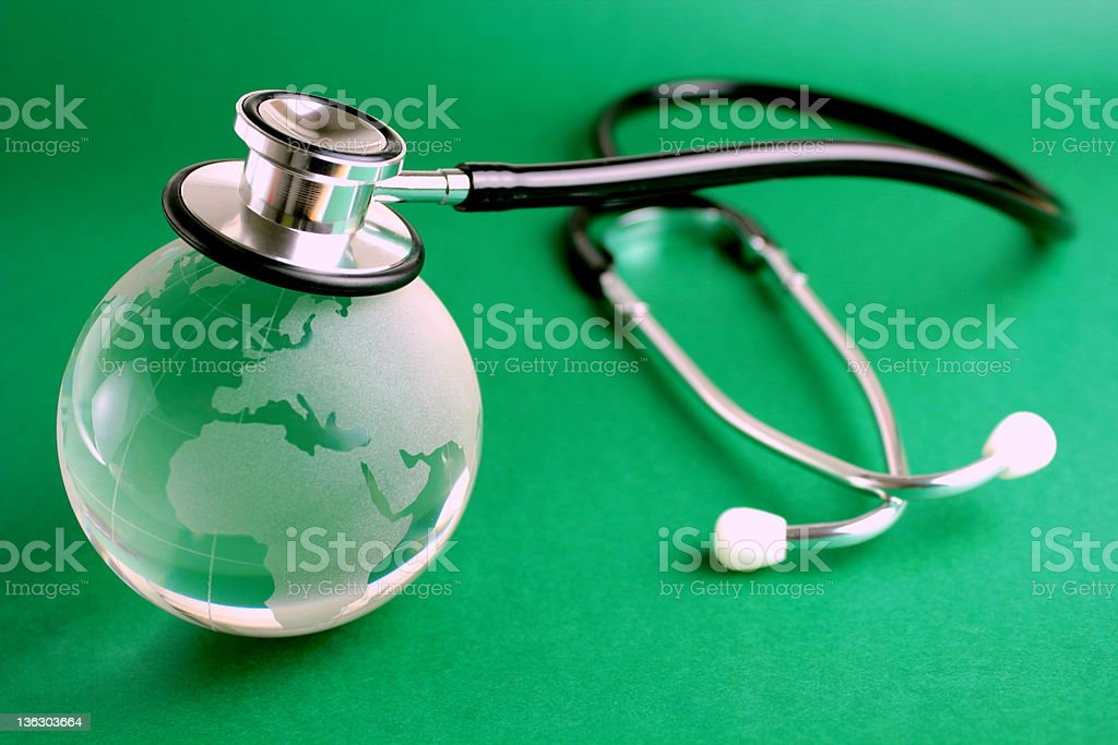 Stethoscope and crystal globe on green background stock photo