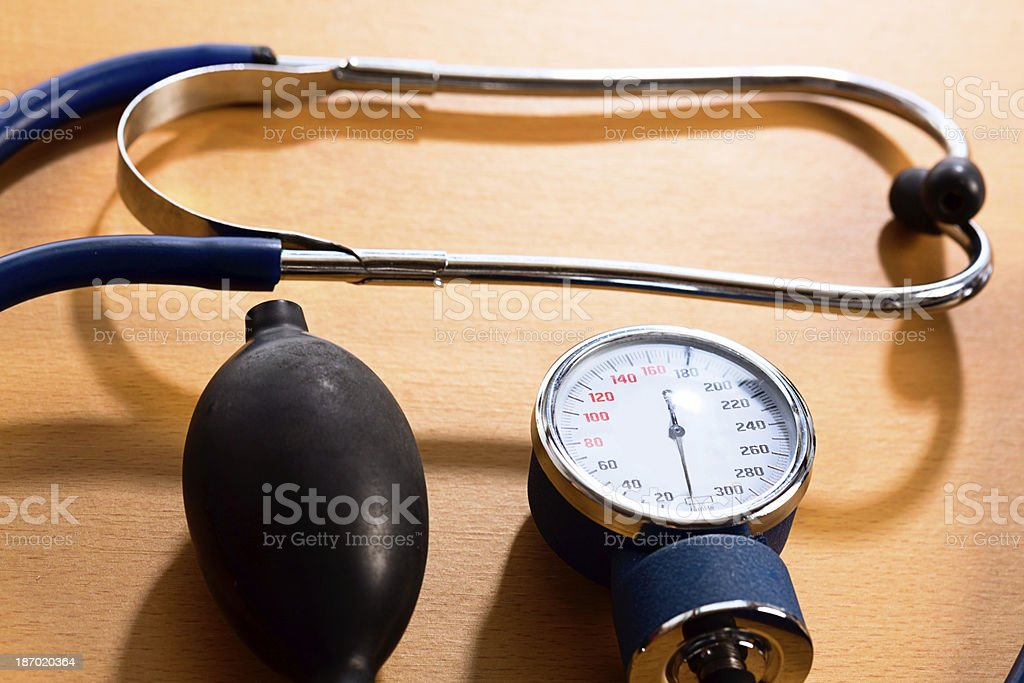 Stethoscope and dial of blood pressure meter on doctor's desk stock photo