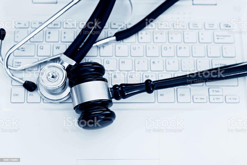 Stethoscope and gavel on keyboard of laptop stock photo