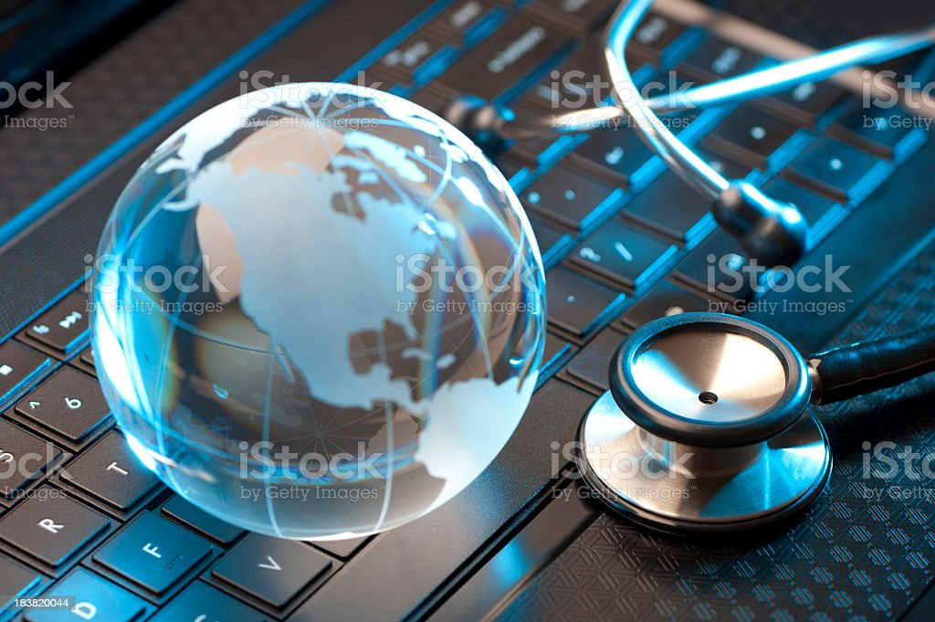 Stethoscope and globe on a laptop stock photo
