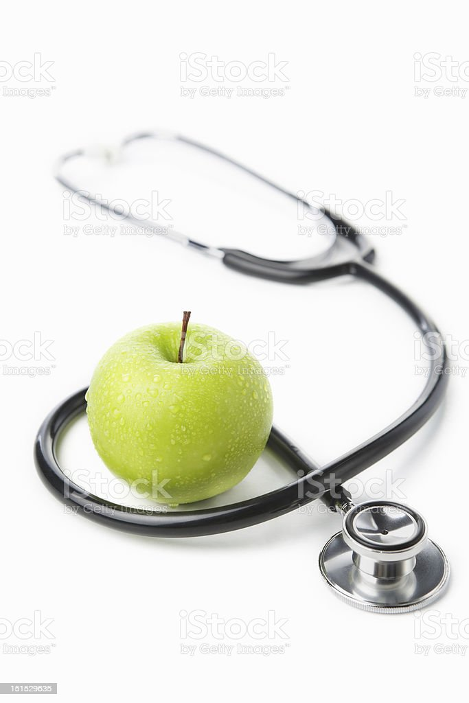 Stethoscope and green apple over white royalty-free stock photo