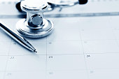 Stethoscope and pen on calendar