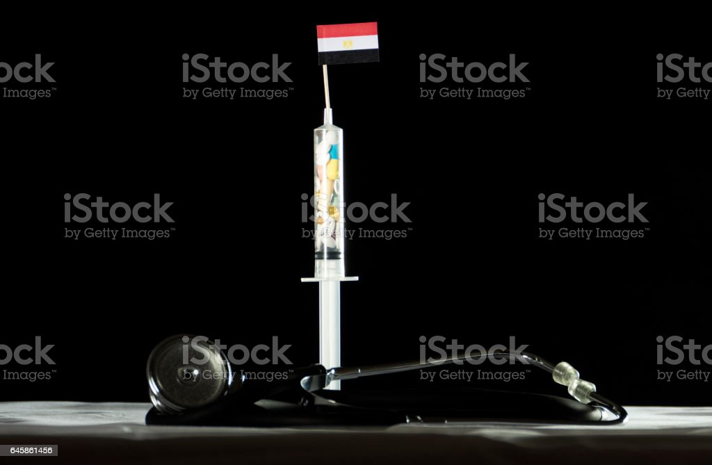 Stethoscope and syringe filled with drugs injecting the Egyptian flag stock photo