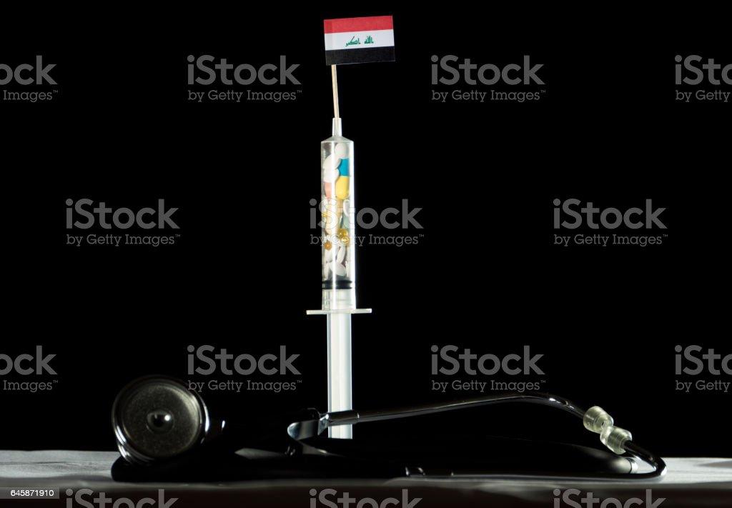 Stethoscope and syringe filled with drugs injecting the Iraqi flag stock photo