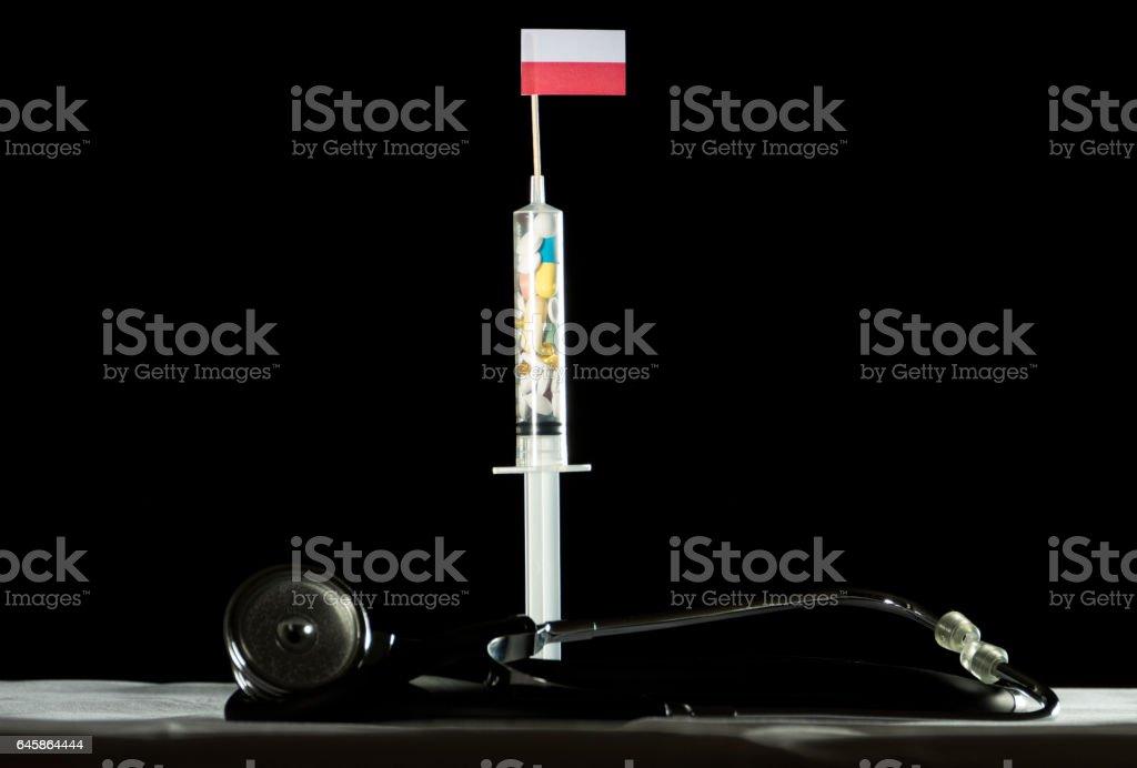 Stethoscope and syringe filled with drugs injecting the Polish flag stock photo