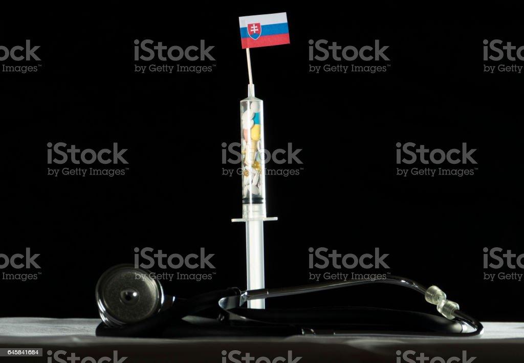 Stethoscope and syringe filled with drugs injecting the Slovakian flag stock photo