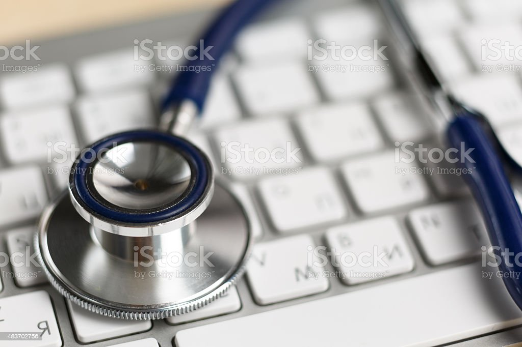 Stethoscope head lying on silver keyboard closeup stock photo