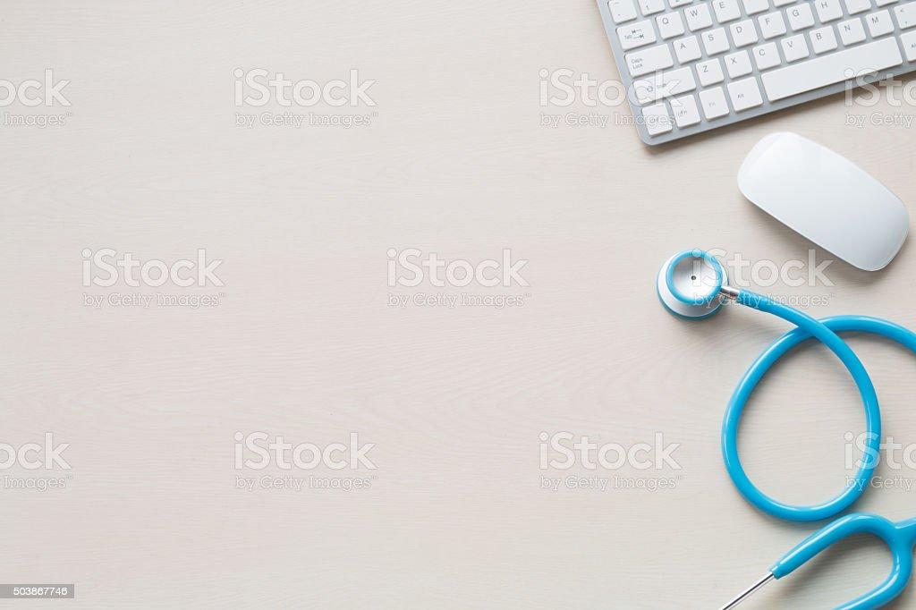Stethoscope in doctors desk stock photo