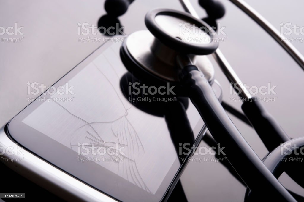 Stethoscope on a cracked smart phone royalty-free stock photo