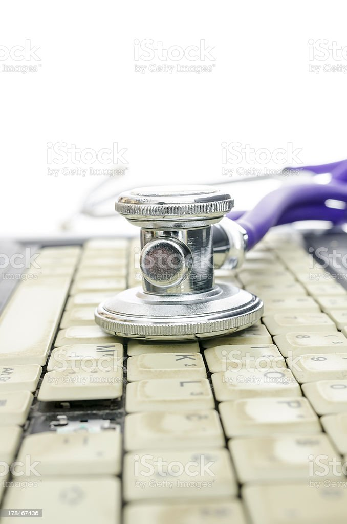 Stethoscope on and old laptop keyboard missing a key stock photo