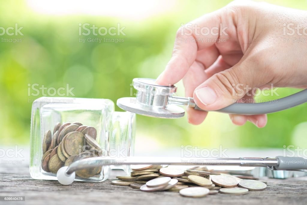 Stethoscope on bottle and coin on wooden background ,Determined stock photo