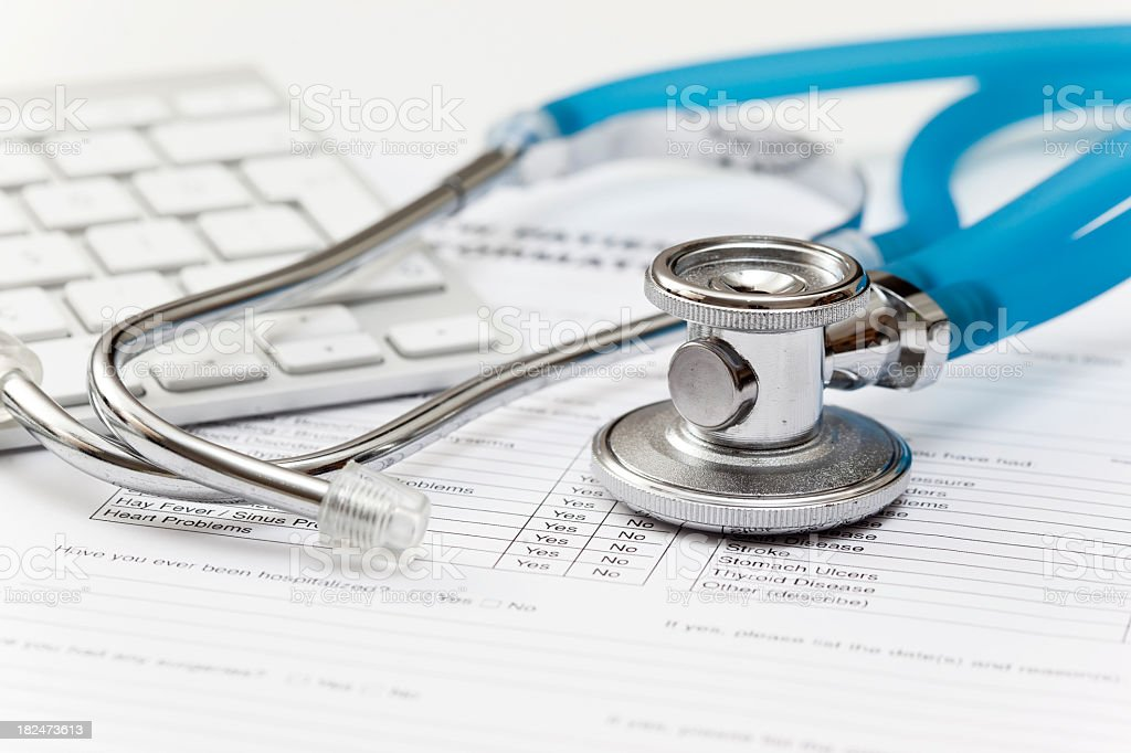 Stethoscope on top of medical questionnaire and keyboard royalty-free stock photo