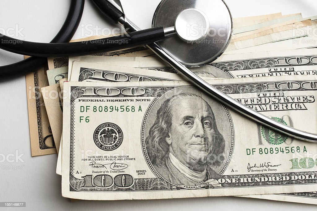 Stethoscope over a pile of $100 US bills on a white surface royalty-free stock photo