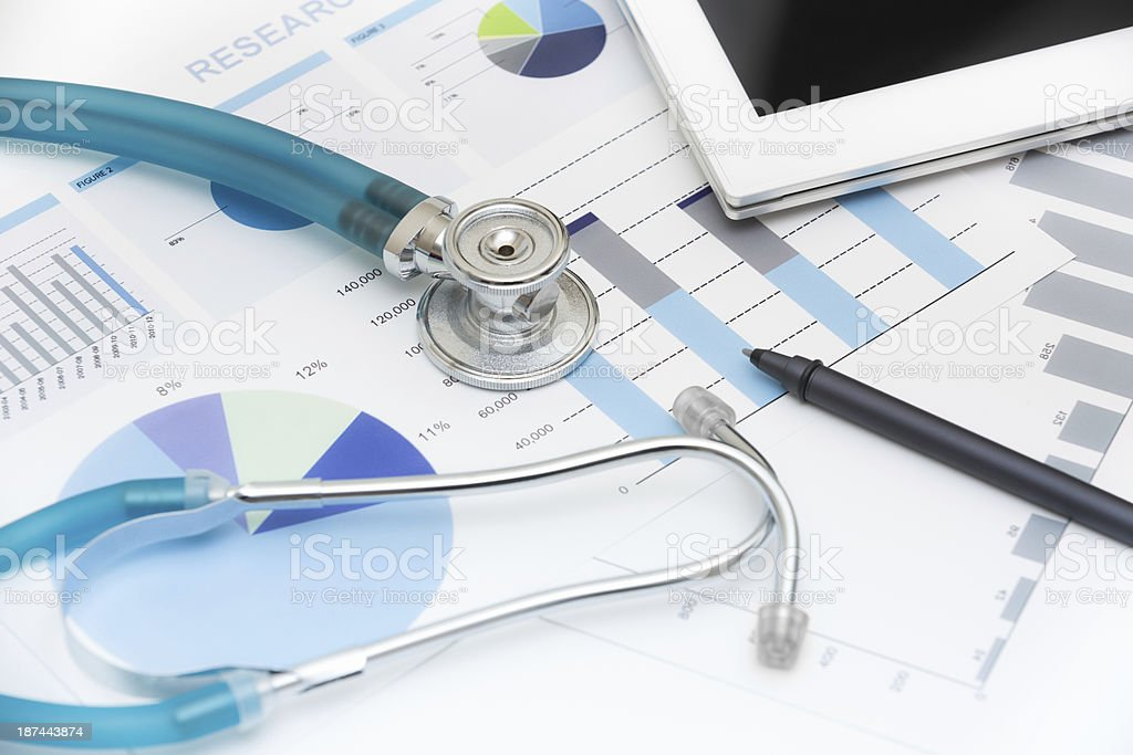 Stethoscope, pen and tablet on report sheets stock photo