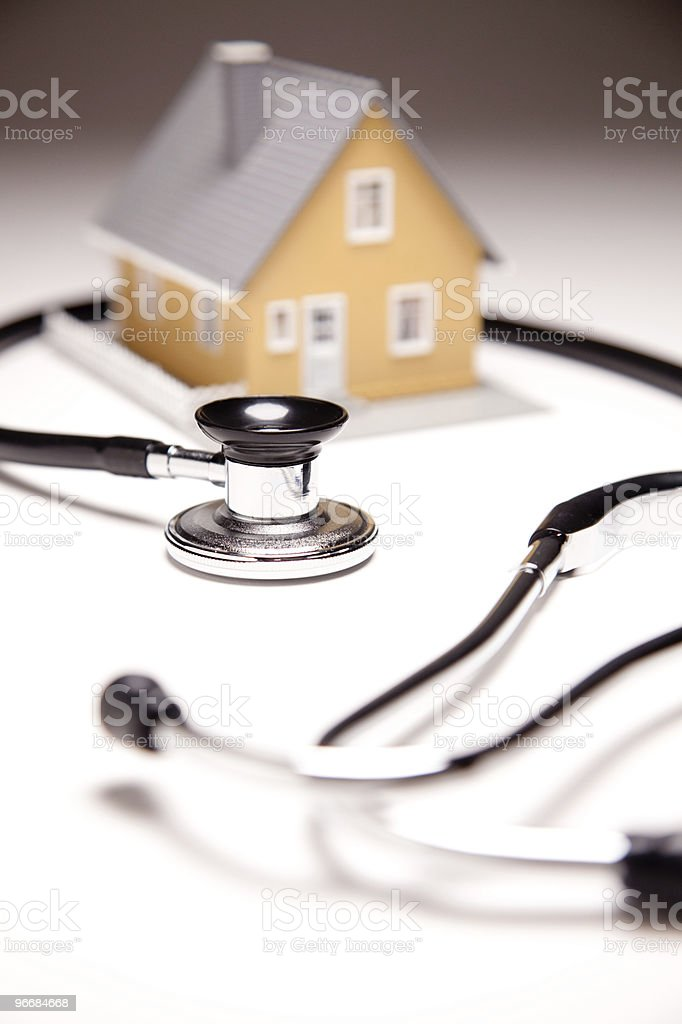 Stethoscope placed around tan and gray miniature model house stock photo