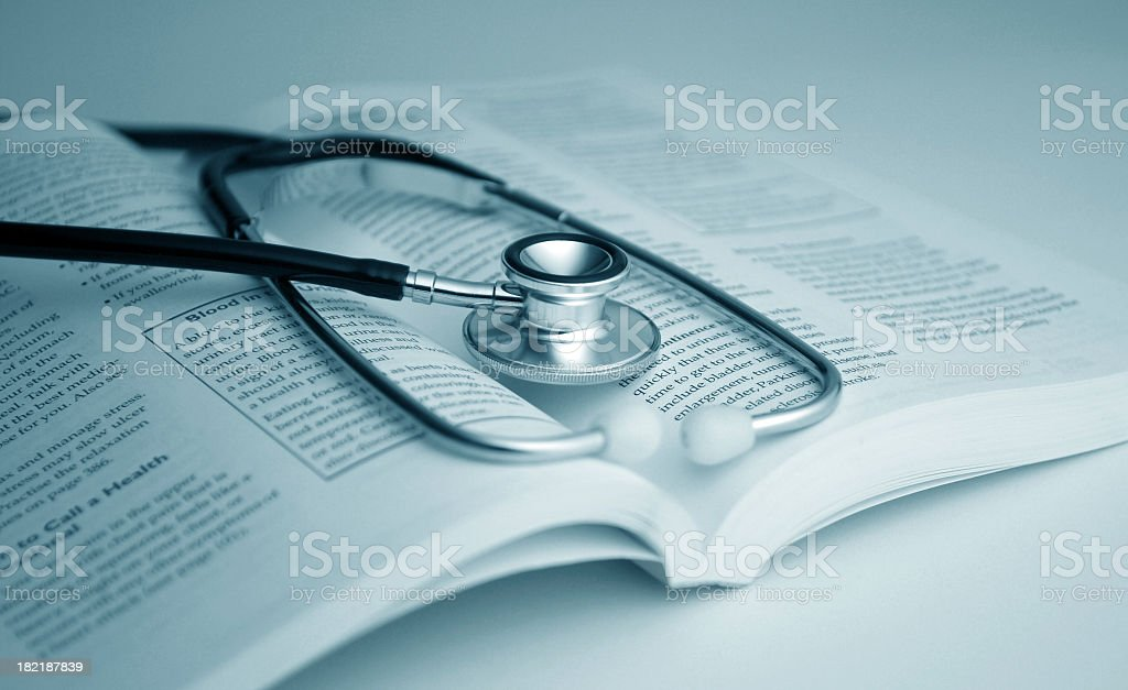 A stethoscope placed on top of an open medical book stock photo