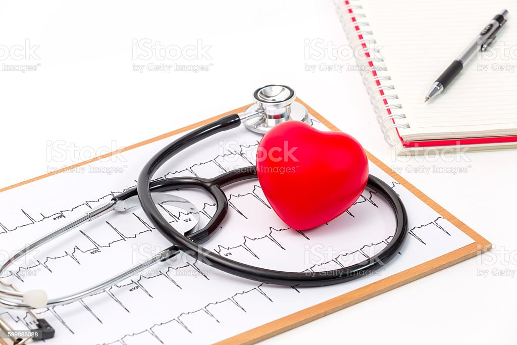 Stethoscope with a red heart on the top of the ECG stock photo