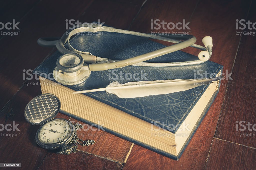 Stethoscope with feather on book and watch stock photo