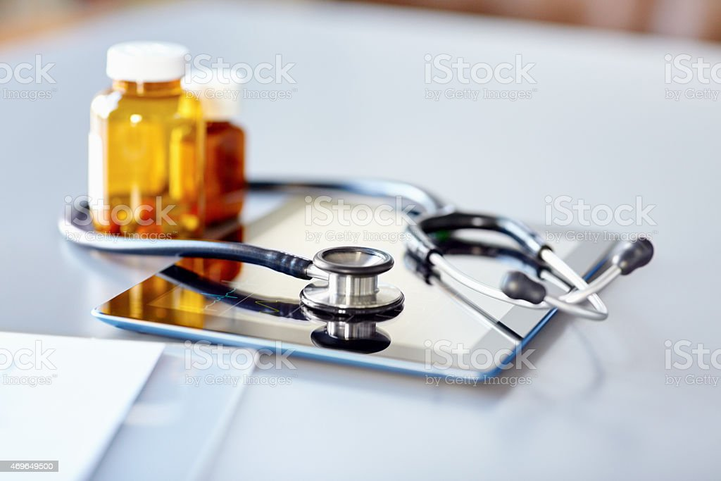 Stethoscope with pill bottle and digital tablet on desk stock photo