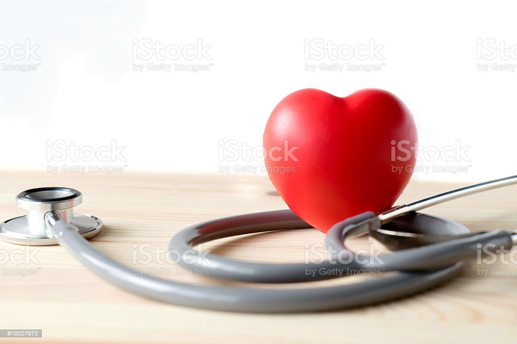 Stethoscope with red heart on a wood background stock photo
