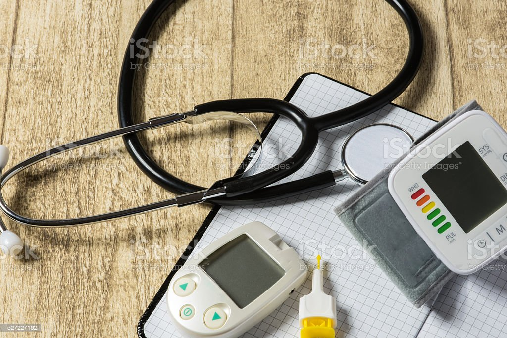 Stethoskope on wooden desk with blood pressure measurement stock photo
