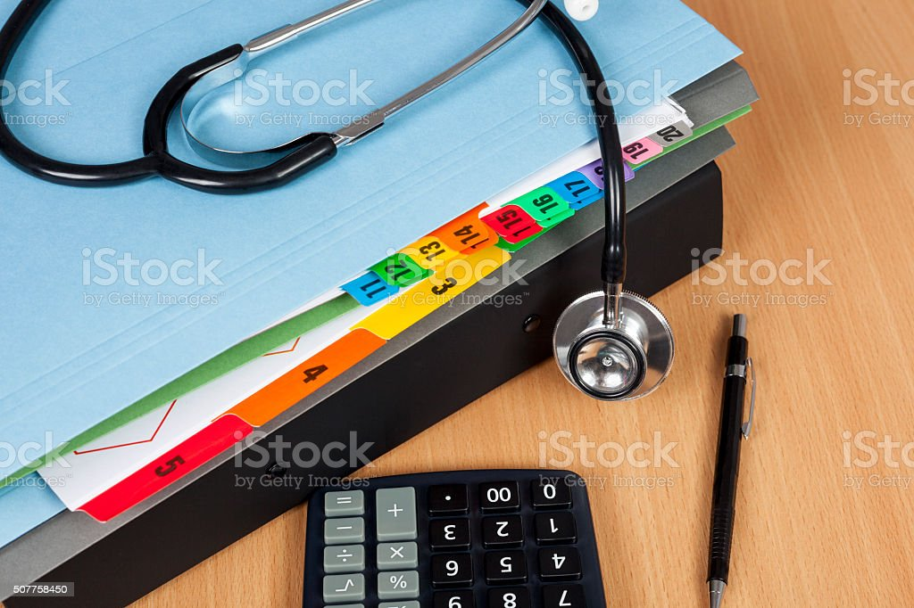 Stethscope laying on a pile of hospital patient records stock photo