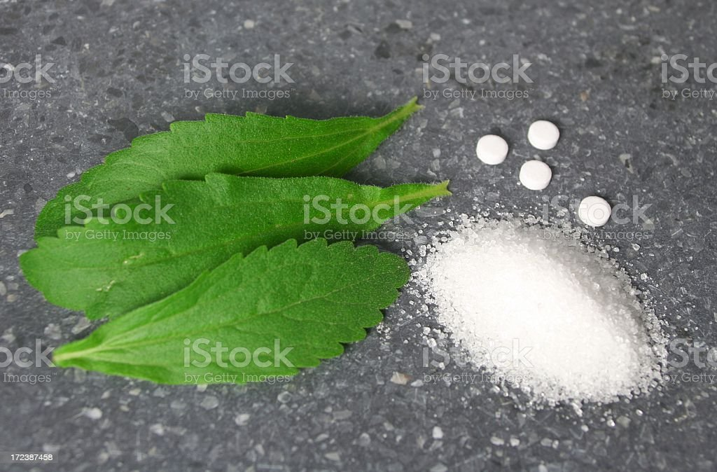 Stevia leaves with pile of sugar stock photo