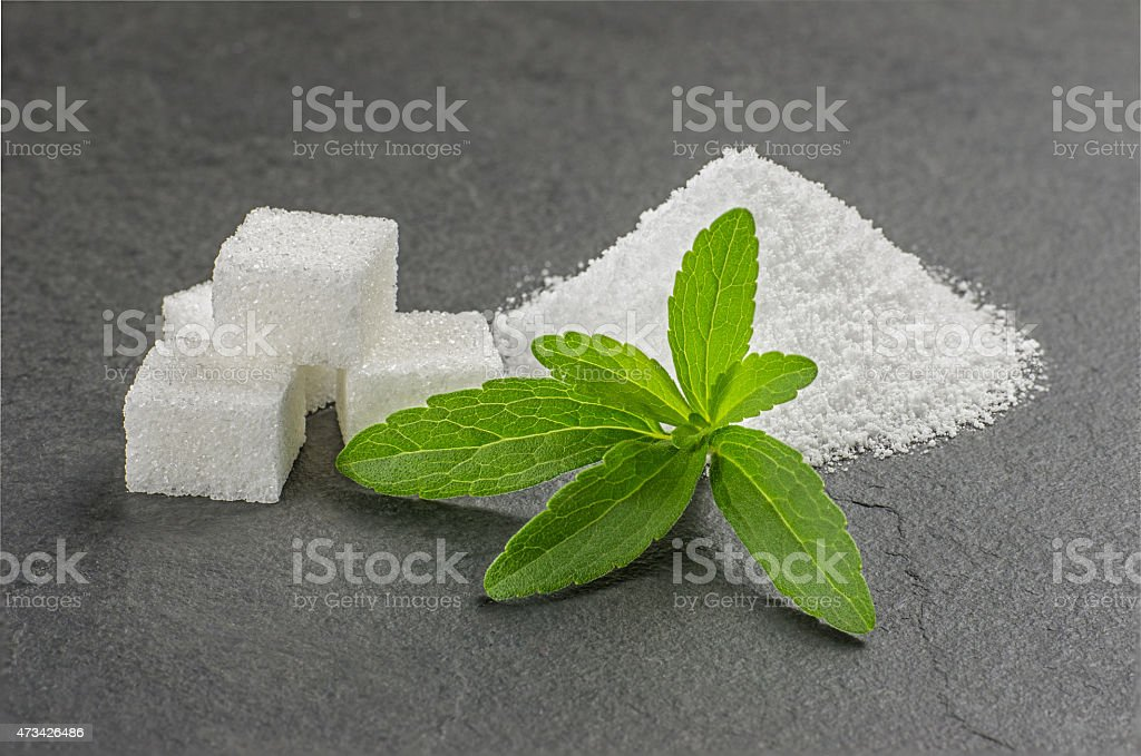 Stevia leaves with stevia powder and sugar cubes stock photo