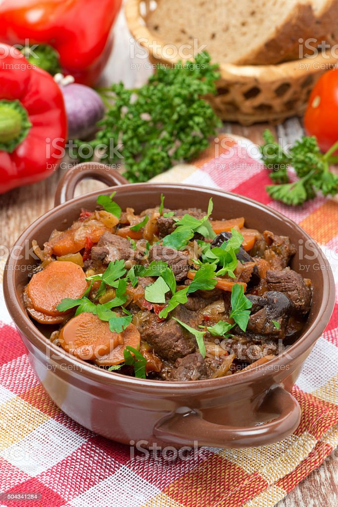 Stew with beef, vegetables and prunes in a saucepan, vertical stock photo