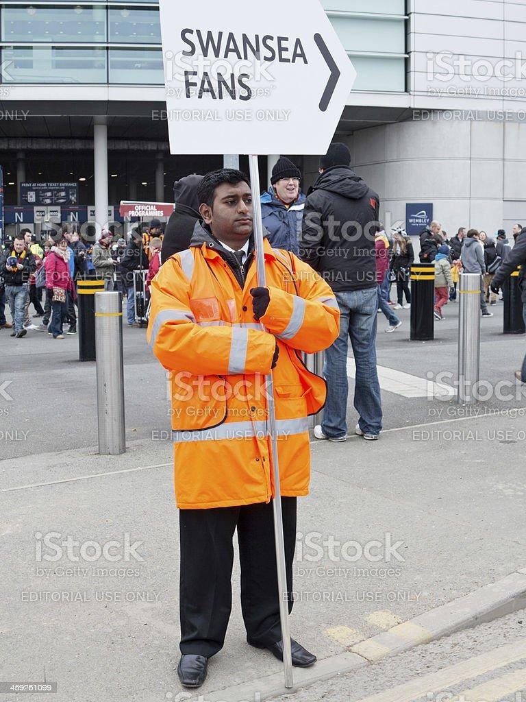 Steward in orange jacket at football stadium entrance stock photo