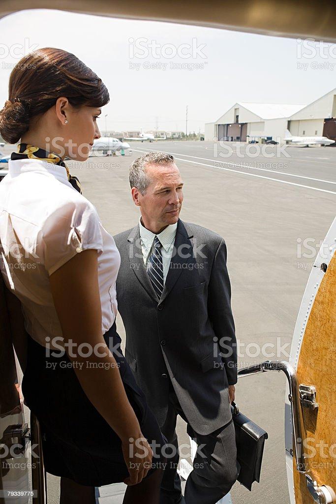 Stewardess and businessman boarding jet royalty-free stock photo