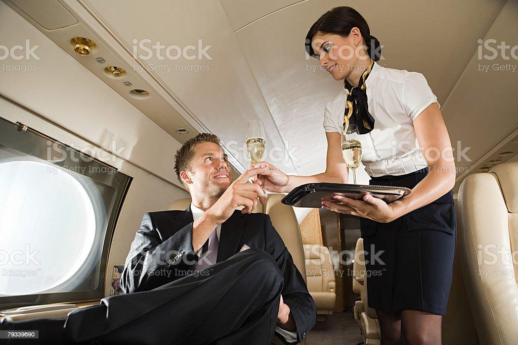 Stewardess handing champagne to man stock photo