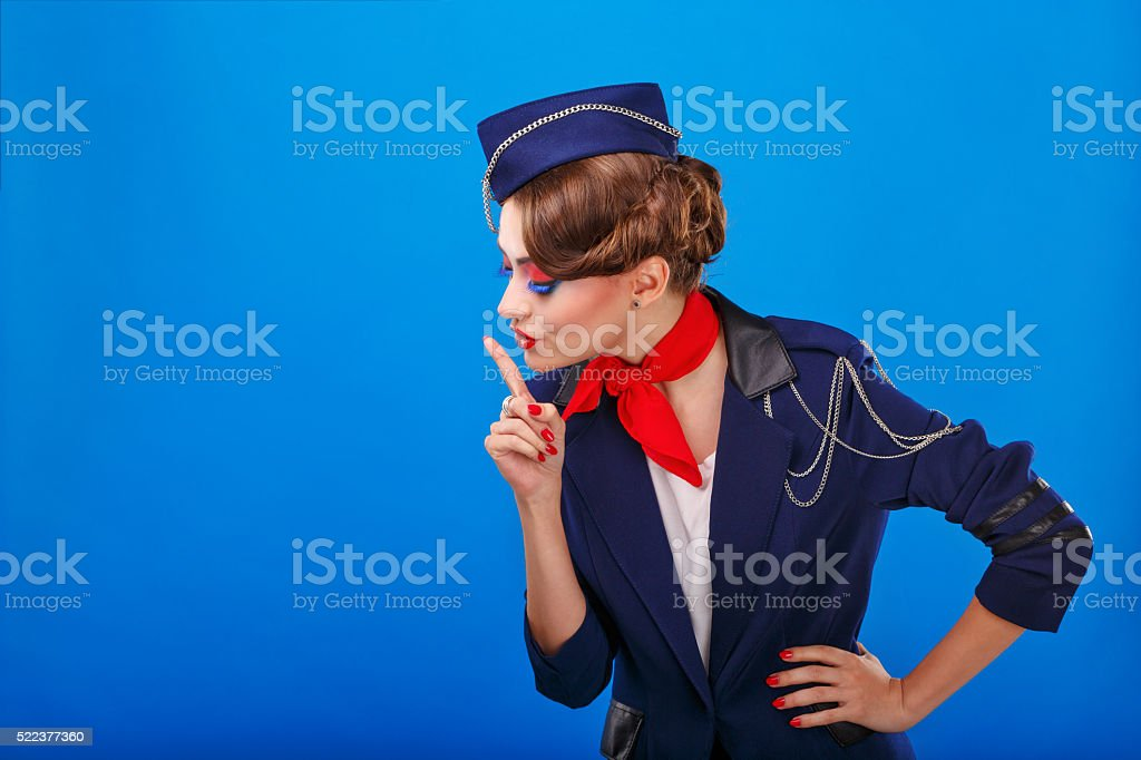 Stewardess with face art asks for silence. stock photo
