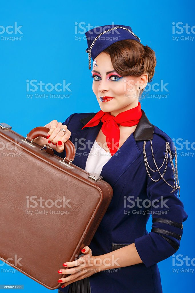 Stewardess with face art holds suitcase. stock photo