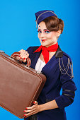 Stewardess with face art holds suitcase.