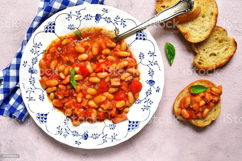 Stewed bean with smoked ham in a tomato sauce.Top view. stock photo
