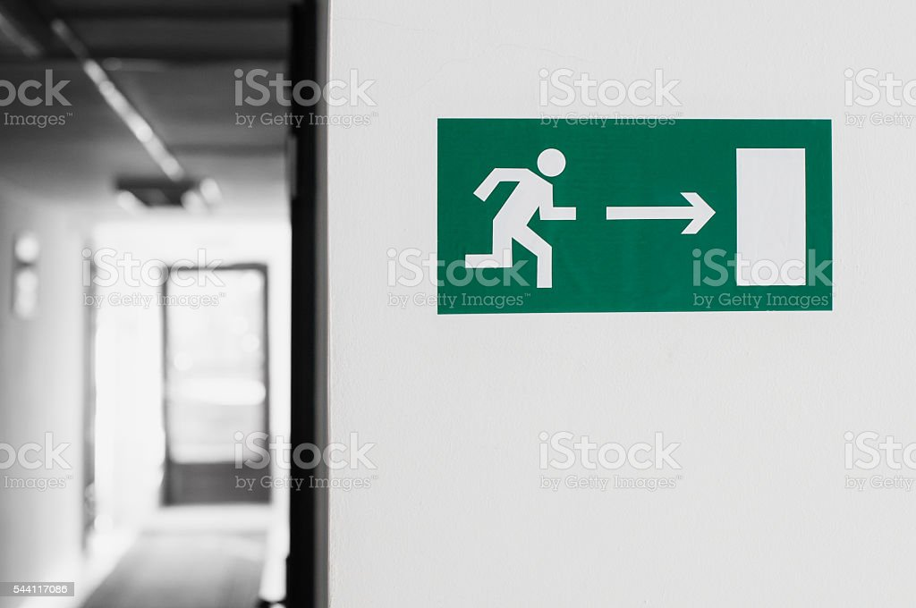 Sticker ' Emergency exit ' hangs on the wall stock photo