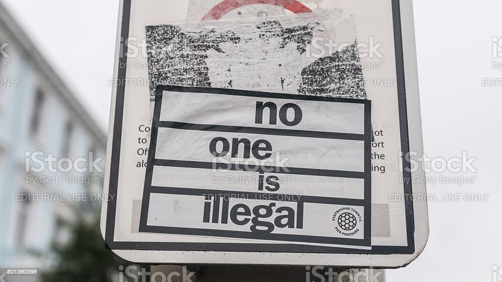 Sticker on street lamp with words 'no one is illegal' stock photo
