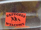 sticker 'Refugees welcome' on the window of building in Maribor