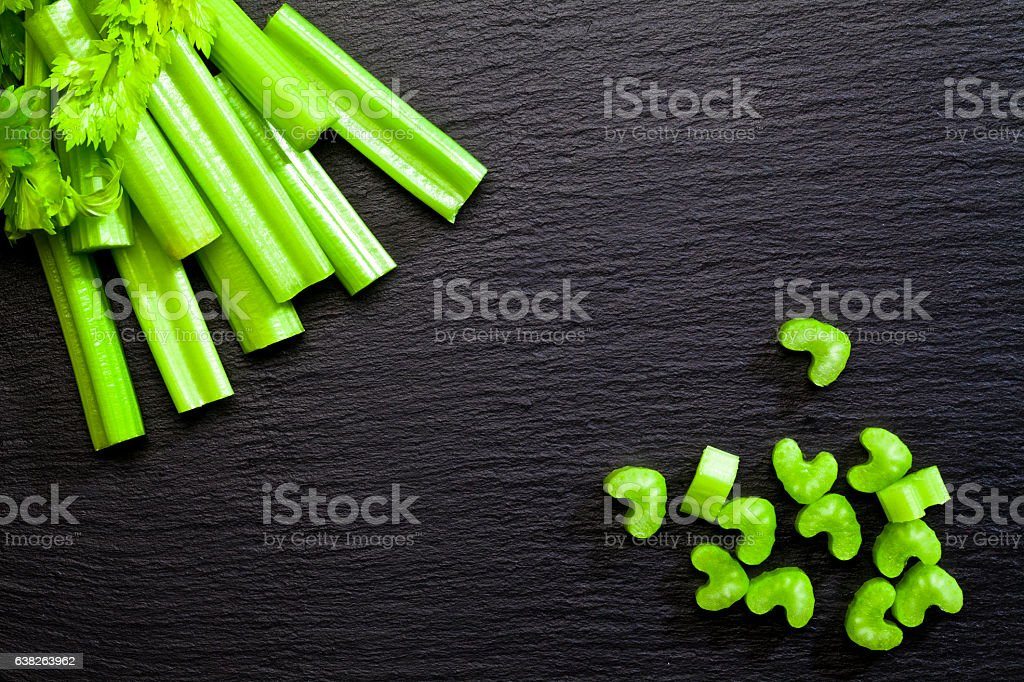 Sticks and chopped celery on dark background stock photo