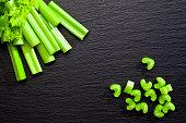 Sticks and chopped celery on dark background