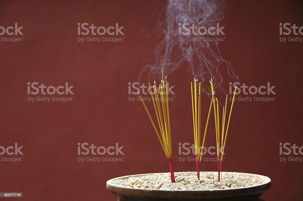 Sticks of burning incense on dark red background stock photo